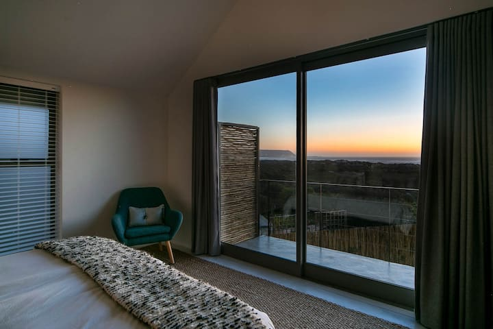 master bedroom with balcony & sea views at sunset