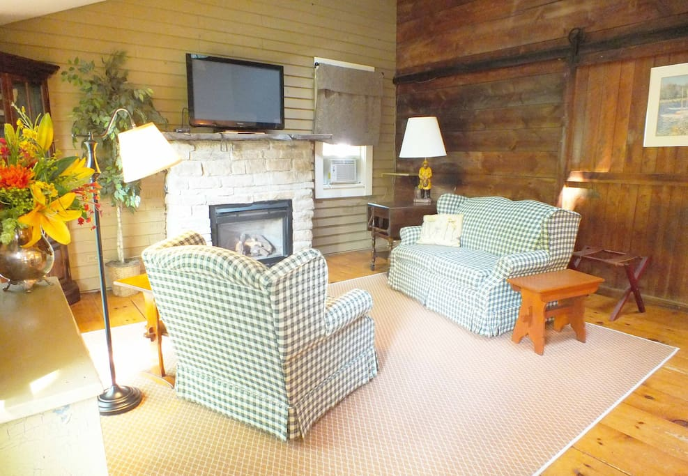 Living room with gas fireplace, cable TV, and original barn door