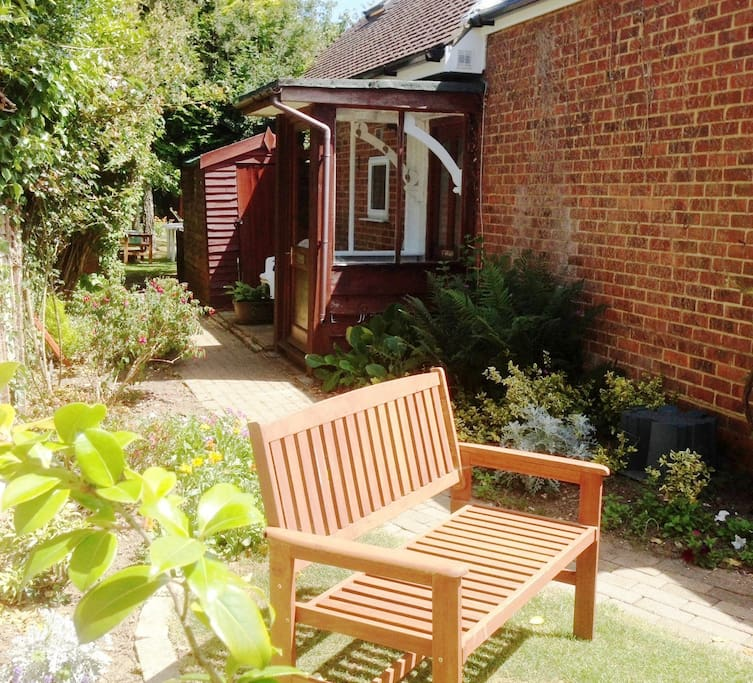 Private garden of holiday let showing entrance porch.