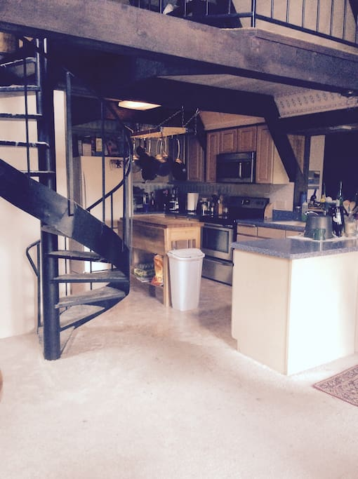 Kitchen with spiral staircase that leads to loft bedroom