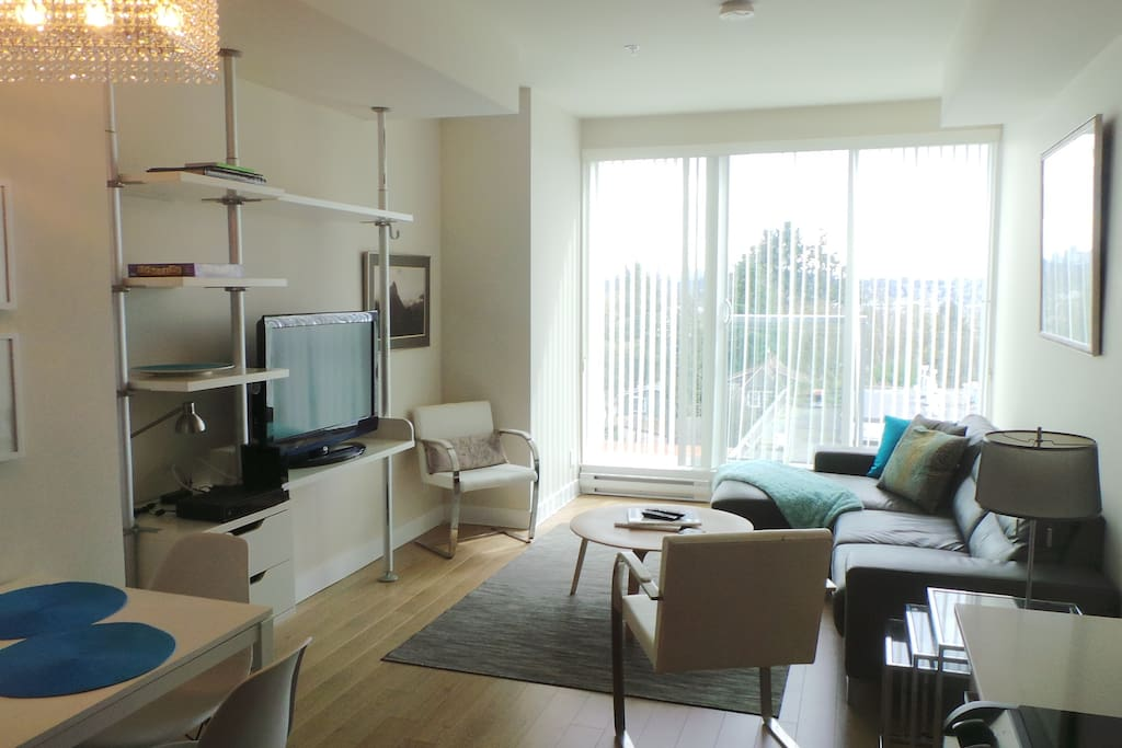 Bright, living area, with dining table, TV &  sectional