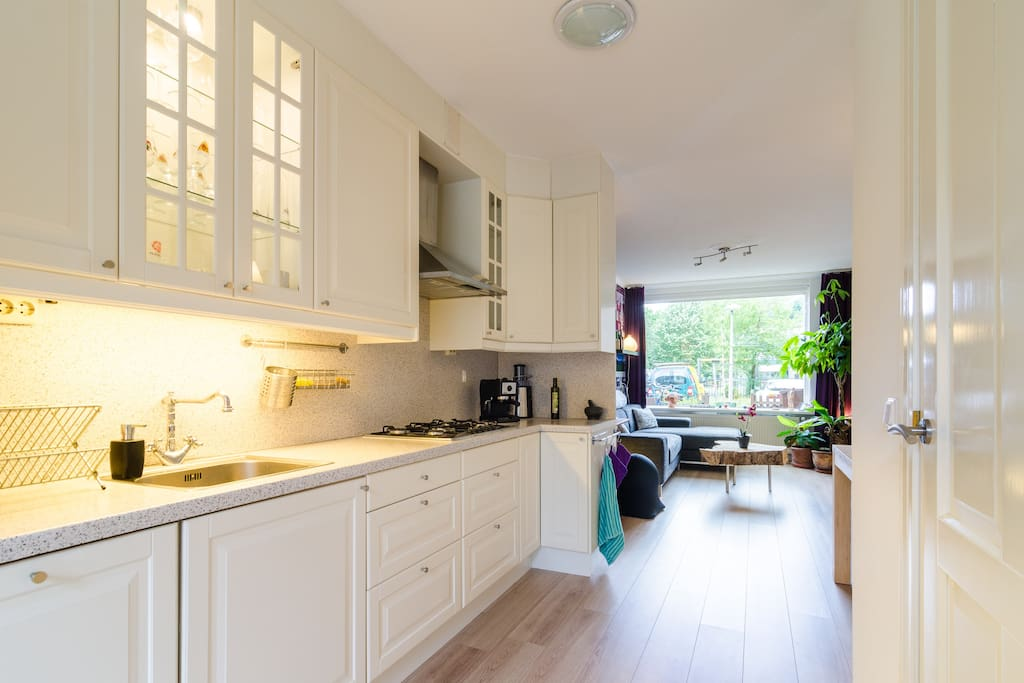 Spacious open kitchen including an espresso machine, small oven, fridge, washing machine and dishwasher.