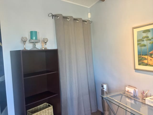 Solid curtain leading to the toilet, basin and shower