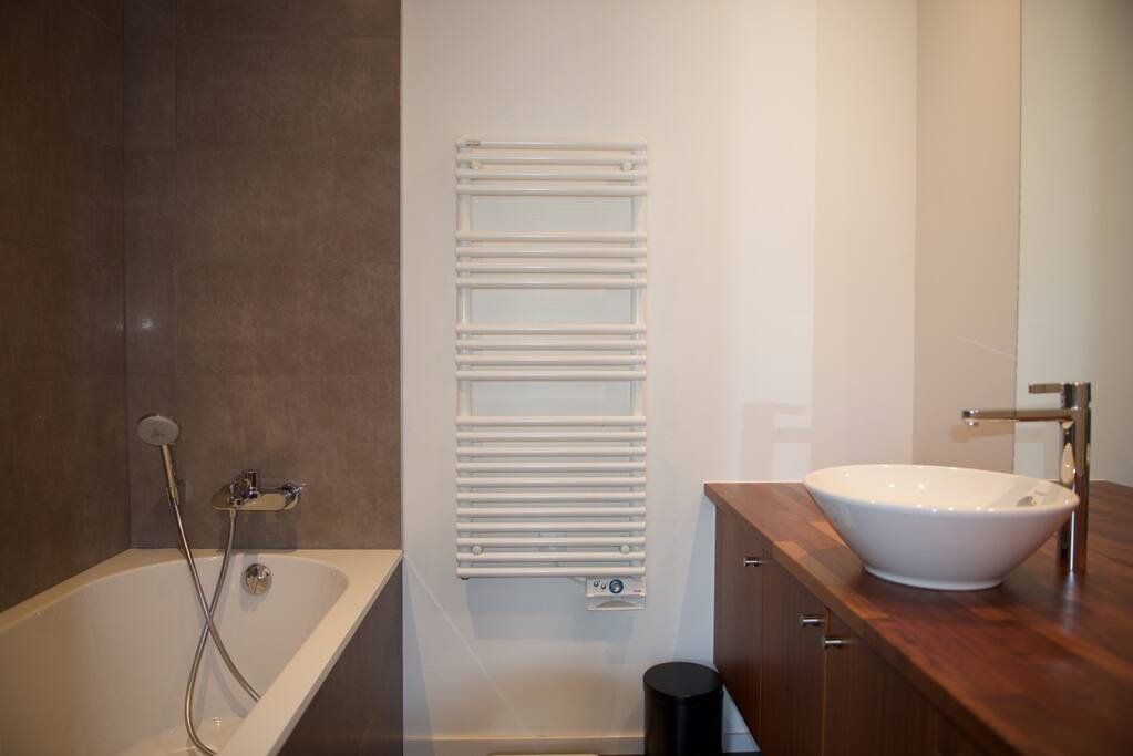 Salle de bain avec baignoire et grand miroir