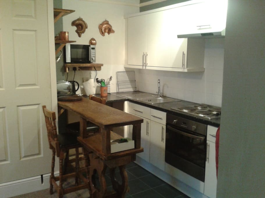 Compact and functional kitchen with fridge, freezer, oven, microwave and a bar