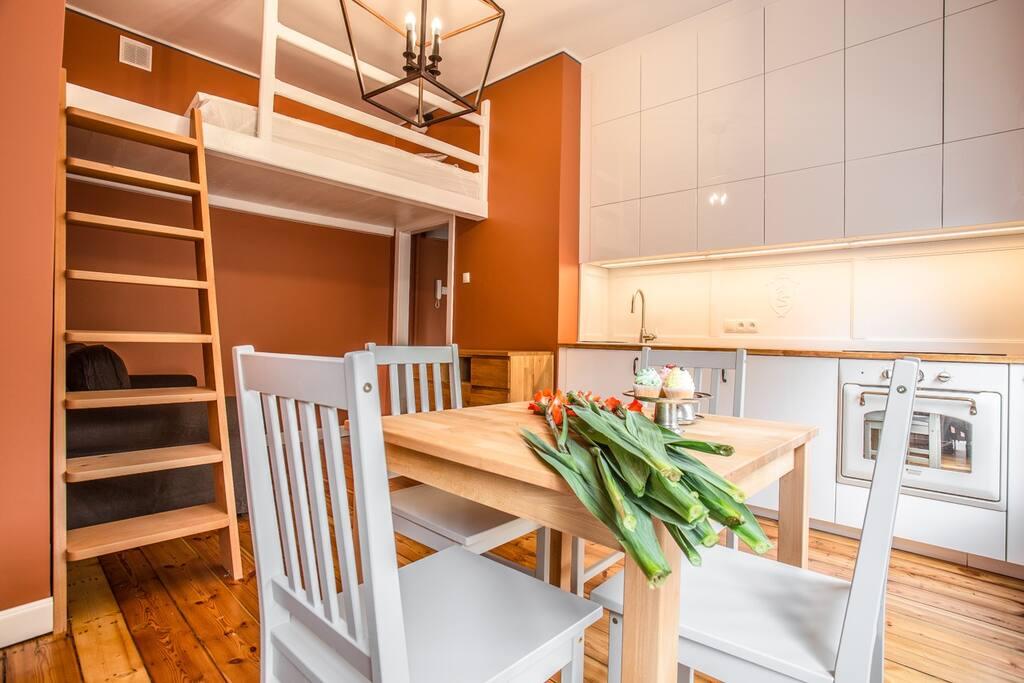 Salon z schodami na antresolę z podwójnym łóżkiem.