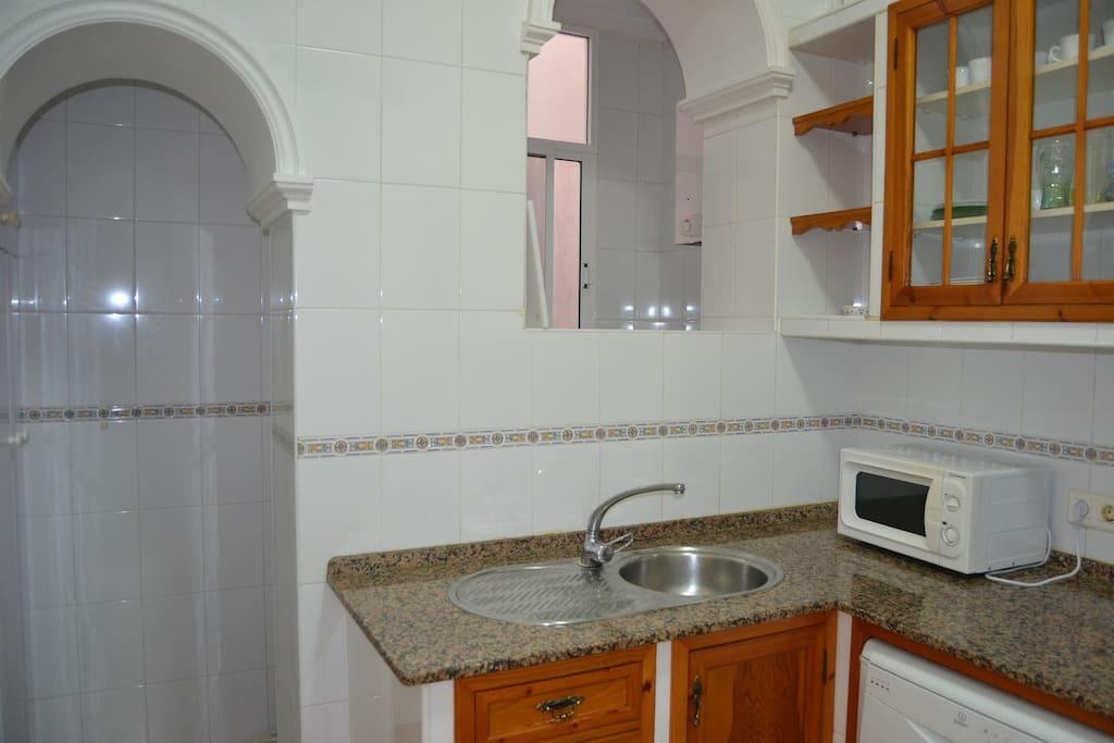 Cocina. Fregadero, microondas y acceso al lavadero