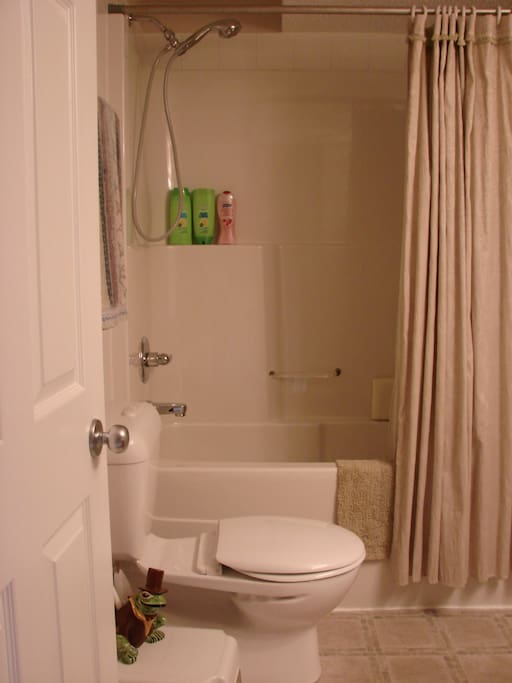 Bathroom - full tub with shower, sink, vanity, and supplies.