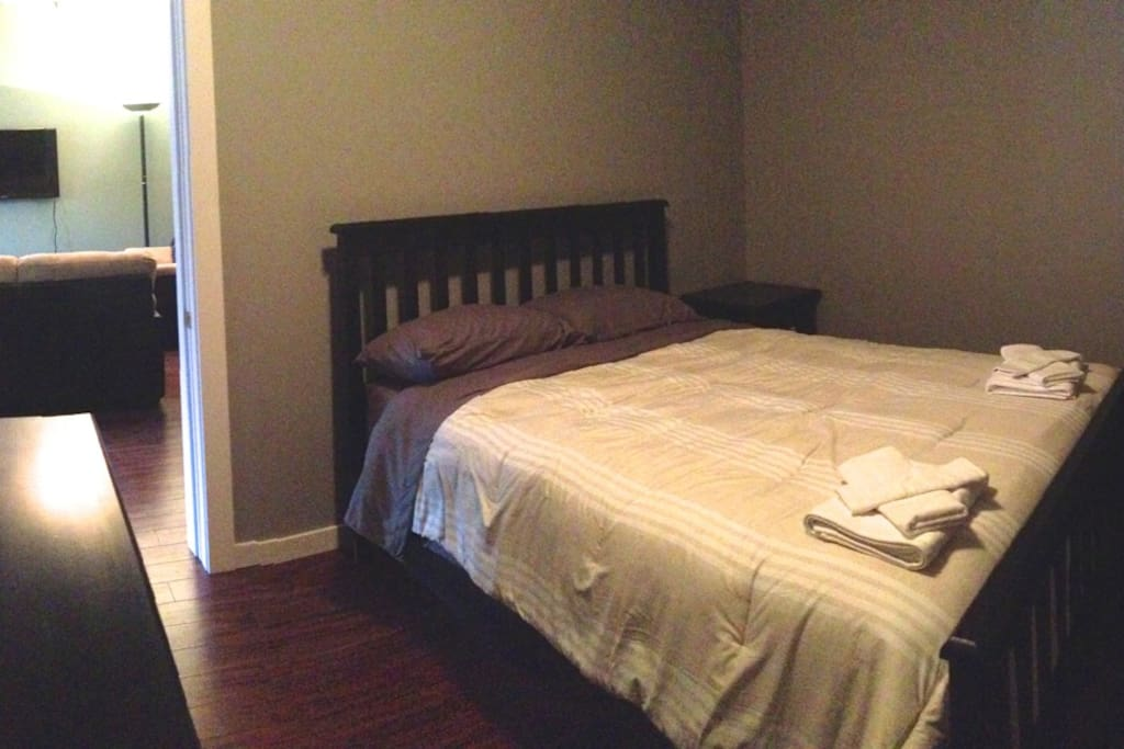 Master bedroom is comfortable with a queen sized bed, hanging space and a large dresser.