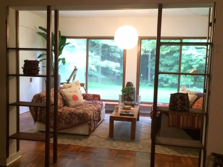 Sunroom facing large back yard. Comfy couches can convert to single beds.