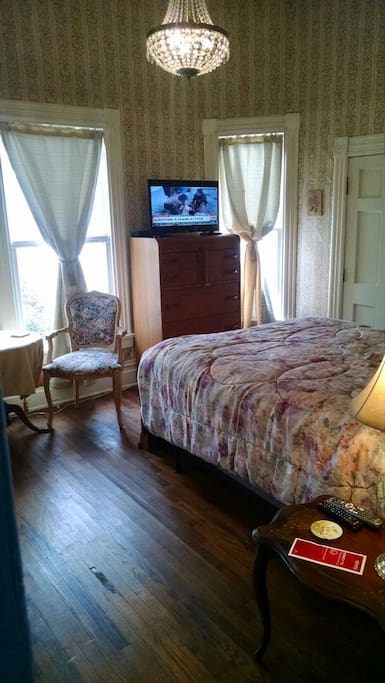 Victorian Rose Room view of queen bed, sitting area, eleven foot Victorian ceiling, and free television with 140 channels and HBO. Wireless Network also free.