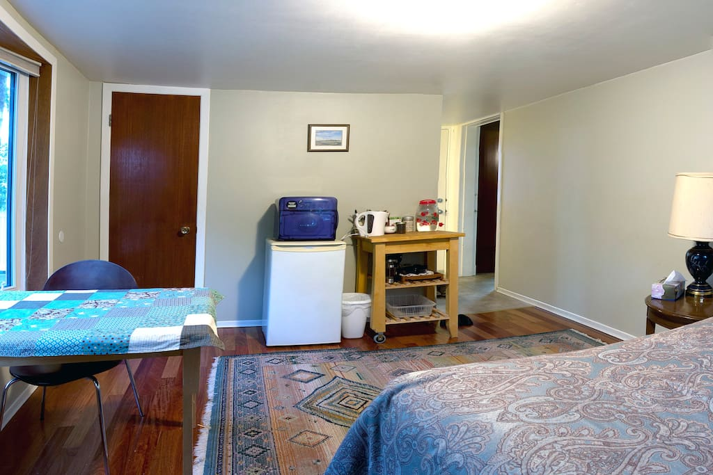 The room includes an expandable table, fridge, microwave and closet.