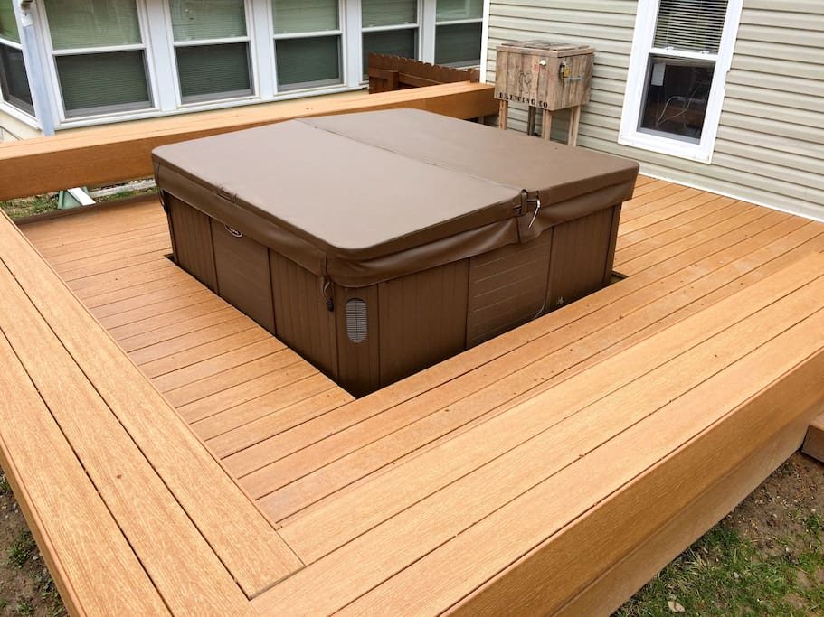 Newly built composite deck and bench surrounding the hot tub.