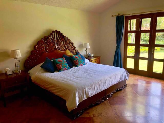 Recámara principal con cama king size, closet, baño completo privado y salida hacia el jardín