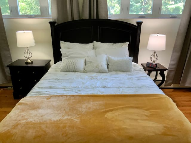 Bedroom 1 - queen bed with two night tables and clock