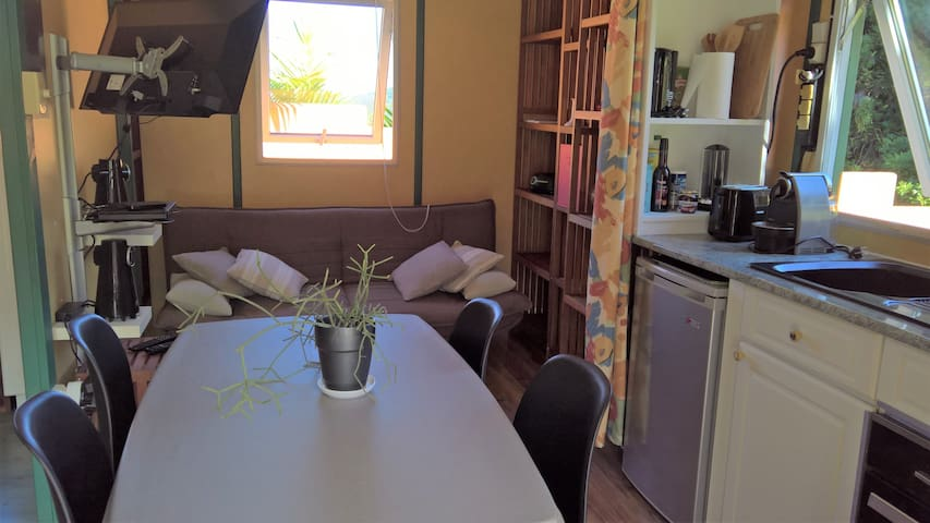 Pièce de vie : salon avec TV, canapé clic-clac, coin cuisine équipée et table à manger donnant sur baie vitrée avec terrasse