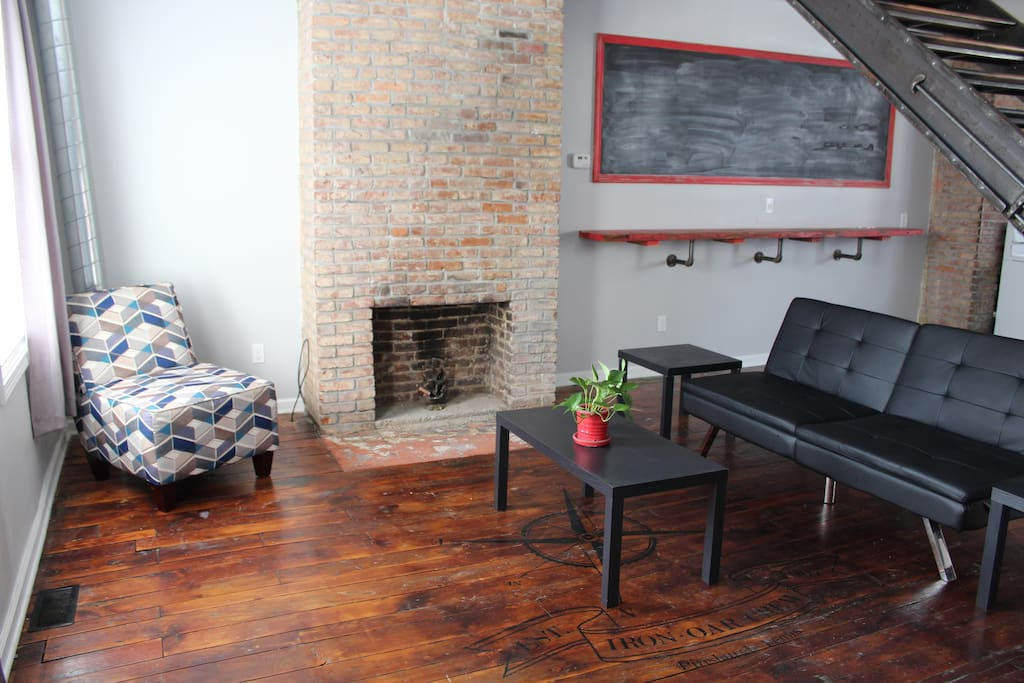 Original hardwoods and exposed brick fireplace in the living room