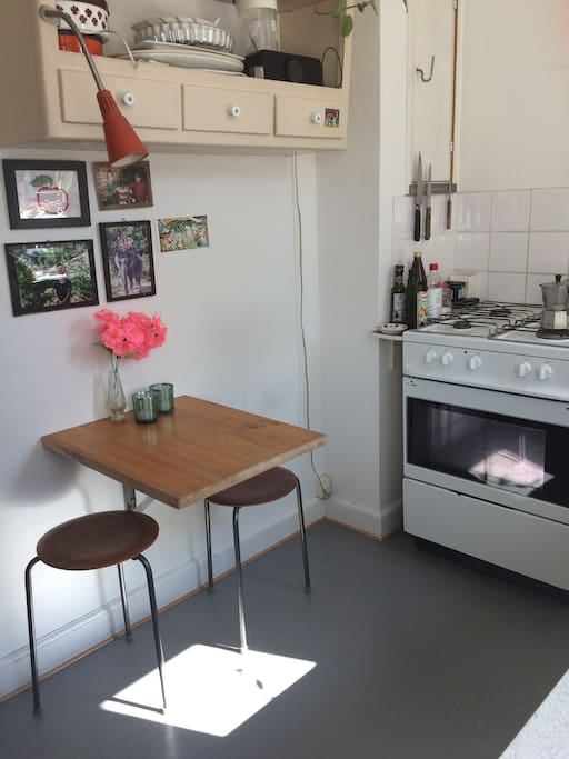 The kitchen also have a small table with two stools.