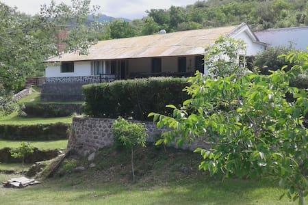 Centenaria casa de adobe rodeada de montañas