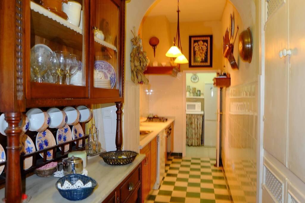Amplia cocina con suelo porcelánico verde y blanco. Equipada