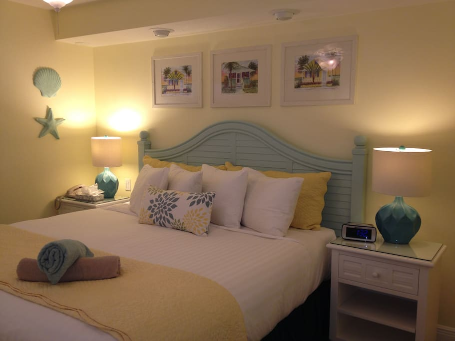 King size bed with crisp 400 Thread Count Linens, Down Pillows and Comforters.