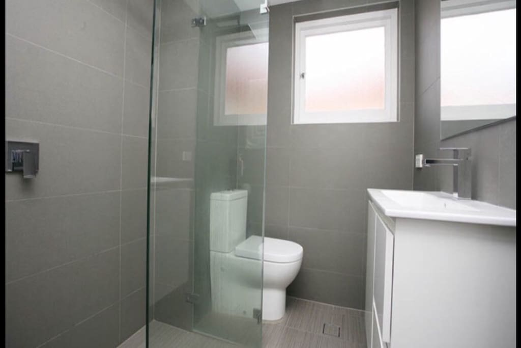 Modern and clean bathroom with large shower and stainless steel features with large mirror and heated towel rack.