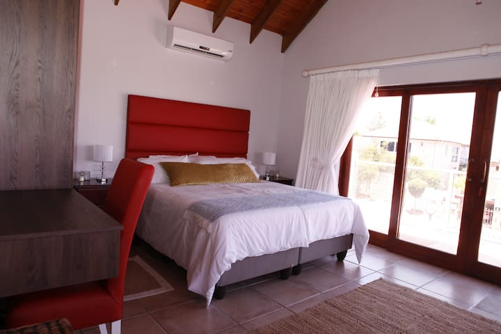 bedroom with aircon  and sliding door to deck with sea and mountain views.