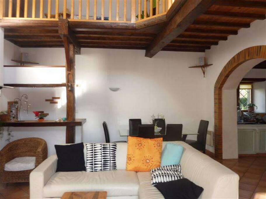 Salon confortable et spacieux avec baie vitrée sur l'extérieur