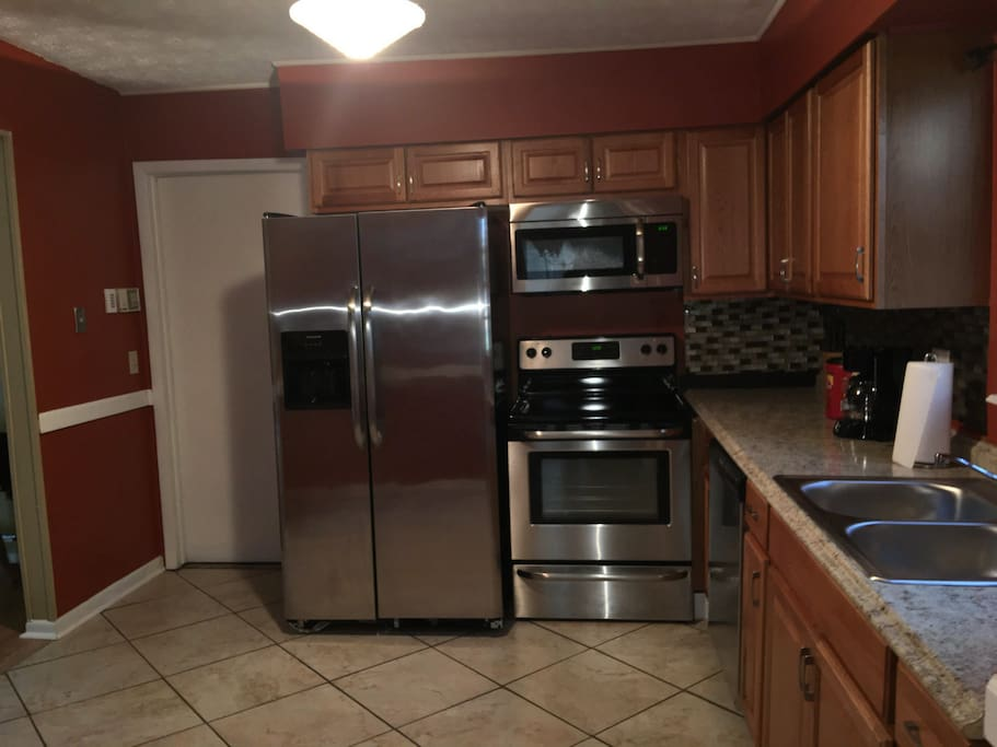 Kitchen with brand new stainless steel appliances refrigerators stove micro wave dishwasher coffee maker toaster and lots of cabinets with luxury back slash.