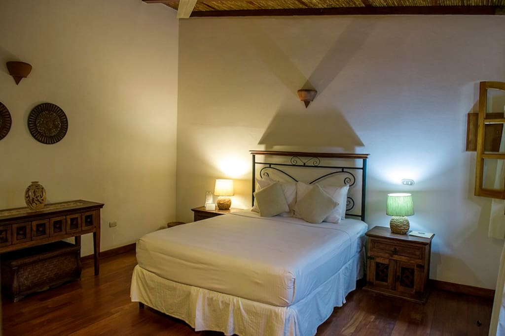 Bedroom with handmade furniture, night tables, wi-fi and ceiling fan.