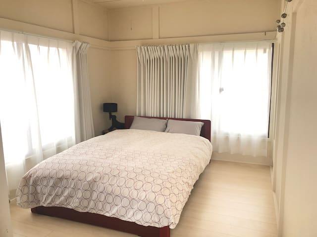 2階のメインゲストルーム(ダブルベッド)。ミラー&チェアー、クローゼット、ソファーあり。エアコン完備