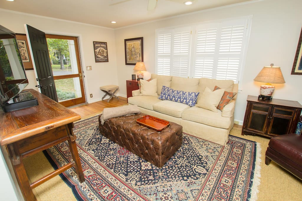Living space with couch and tv as well as open screen door for warm weather months.