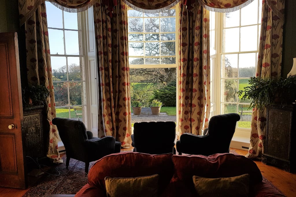 The Drawing room looking out onto the garden on a sunny evening