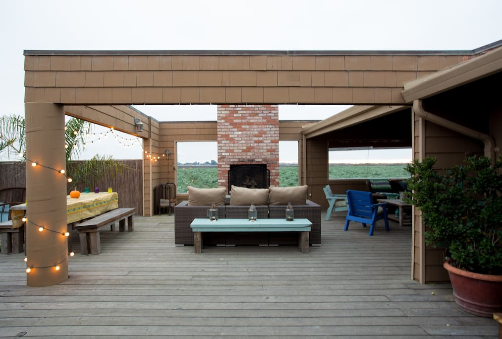 Patio area with views of artichoke fields, fireplace, grill, fountain, and lounge area
