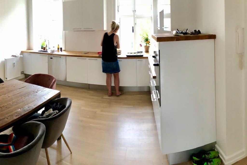 Køkken med opvaskemaskine og spisebord med 5 stole