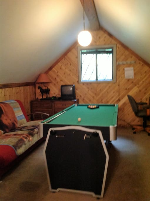 Loft with 7 ft. pool table, futon bed, dresser and office desk.