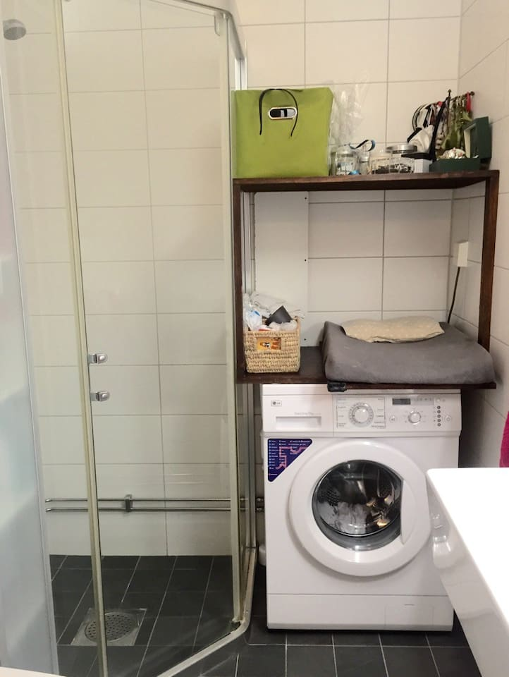 Bathroom with toilet, shower and a washing machine. Also a changing table.