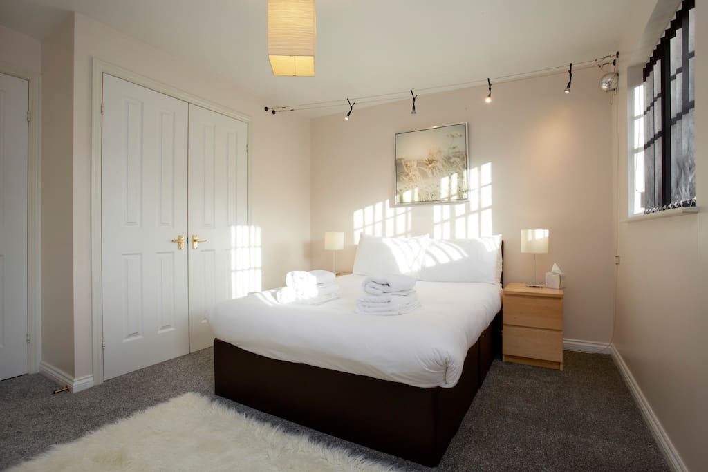 Main bedroom with spot lights, fluffy white rug and built in wardrobes