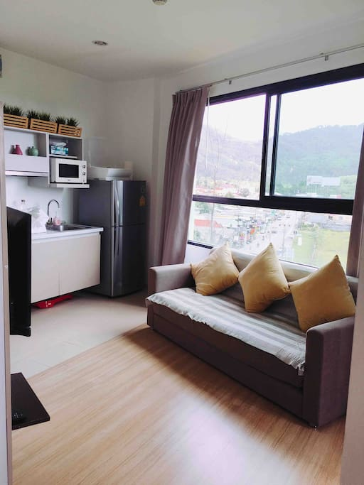 Spacious living space with built-in kitchen, TV stand, shoe cabinet and small dining area.