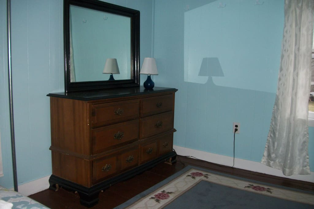 Dresser in Blue Bedroom.   While this room has no closet, there are plenty of coathooks on the wall to hang clothes.