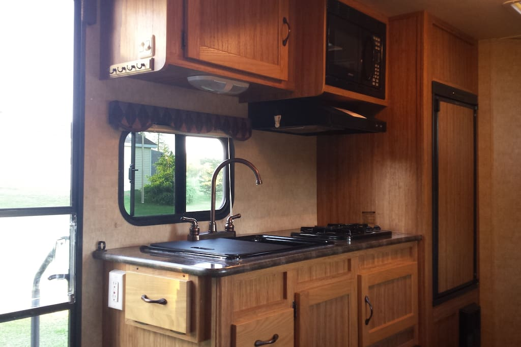Kitchen with fridge, double propane burner, microwave, and sink.