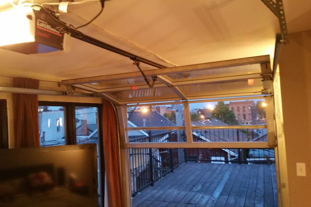 glass overhead door at the foot of the bed opens to private rooftop deck with amazing skyline views