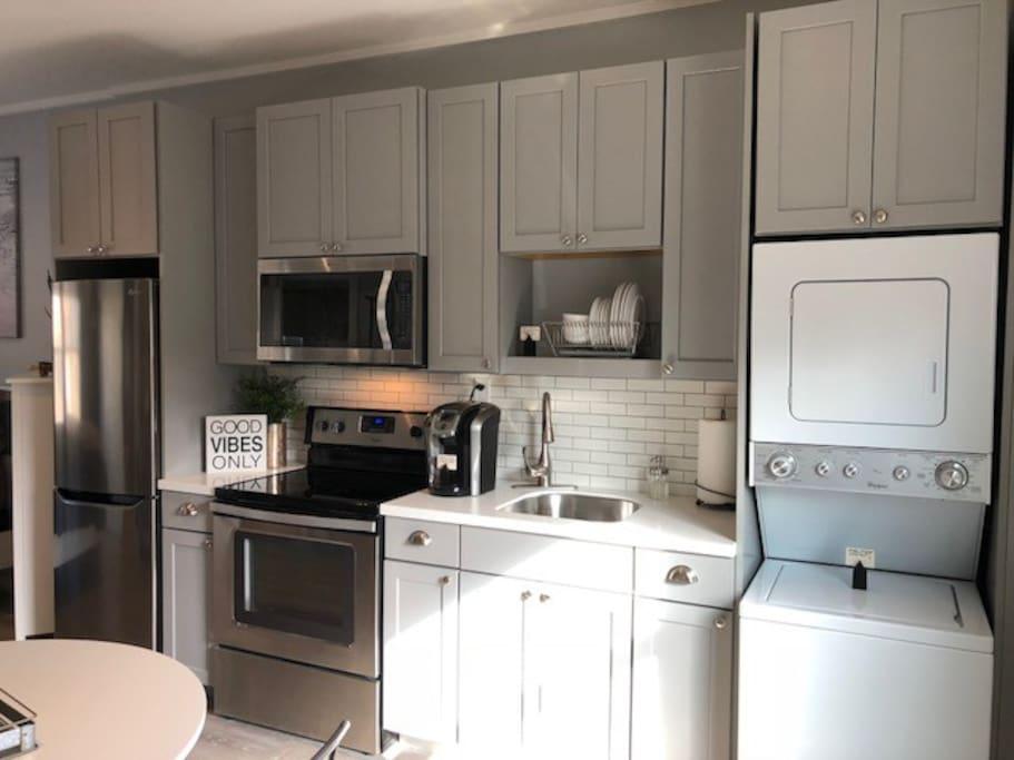 Stainless steel appliances in kitchen w/Stacked Washer & Dryer
