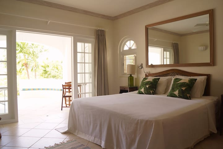 Bedroom 1 has a king bed, overhead fan, aircon, en suite bathroom and French doors leading to the lower terrace and garden