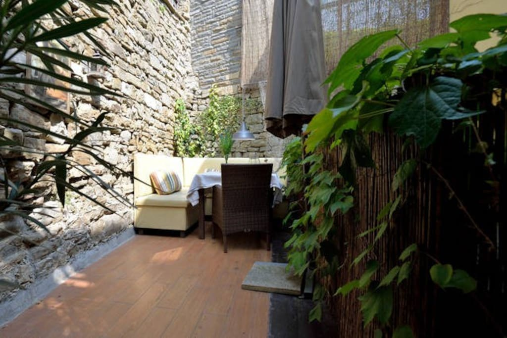 Little, cosy terrace under the ancient stone wall.