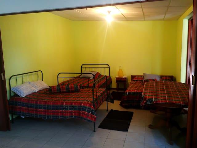 Quarto 3 com 3 camas ,mesinha de cabeceira e mesa grande.