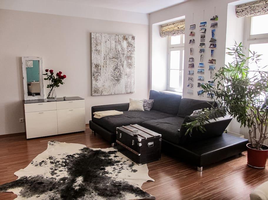 Ein großes Sofa mit ausziehbarem Teil lädt herrlich zum Entspannen und Plaudern ein.