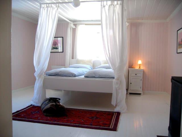 Master bedroom med himmelseng. Rommet har også egen vedovn.