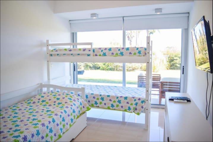 Segundo dormitorio con 4 camas y TV