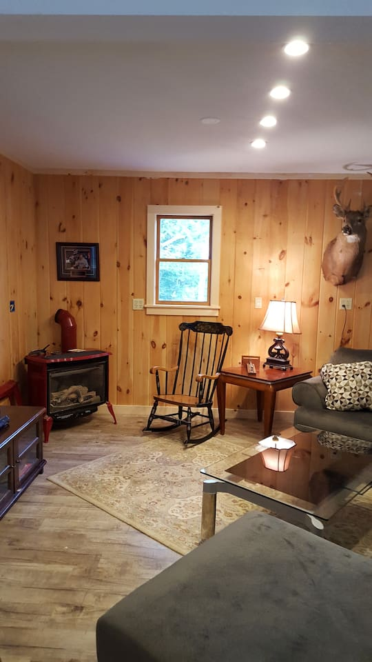 Great Room with gas stove, entertainment center, and large antique dining table